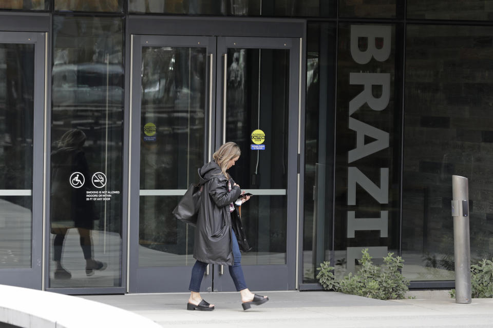 A woman walks near an entrance to the Brazil Building on Amazon's Seattle campus, Wednesday, March 4, 2020, in Seattle. On Tuesday, an Amazon spokesperson said an employee who worked in the building had tested positive for the COVID-19 coronavirus. (AP Photo/Ted S. Warren)