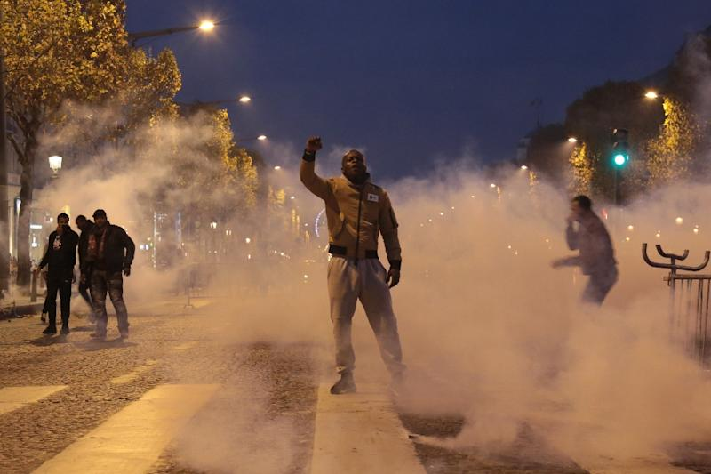 "A demonstrator, standing through the smoke from tear gas, raises his fist during a march against ""slavery in Libya"" on the Champs-Elysees avenue face antiriot police in Paris on November 18, 2017"