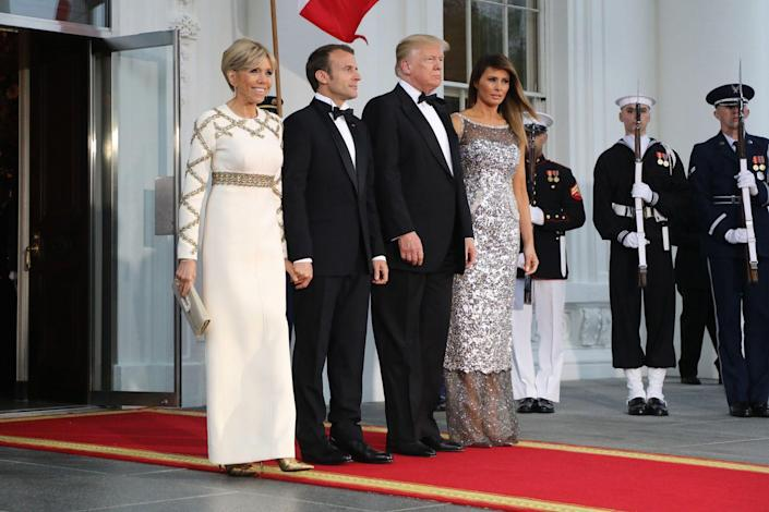 <p>For the black-tie event, Melania wore a black Chanel Chantilly lace haute couture gown that was hand-painted with silver and embroidered with crystal and sequins, while Brigitte wore a white Louis Vuitton dress with gold embroidery.</p>