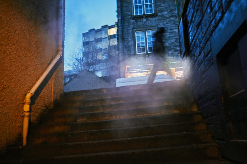 Photographing through exhaust vent steam, condensation from building heating that is illuminated by orange street light. Edinburgh at night has an ominous film noir atmosphere
