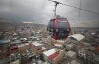 A woman, wearing a protective face mask as a precaution against the new coronavirus, rides in a public cable car in Bogota, Colombia, Wednesday, April 1, 2020, during a countrywide lockdown as it seeks to prevent the spread of the COVID-19. (AP Photo/Fernando Vergara)