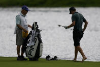 Brandon Hagy moves to put his shoes back on after he hits from the rough beside a water hazard on the fifth hole in the first round of play at the Northern Trust golf tournament, Thursday, Aug. 19, 2021, at Liberty National Golf Course in Jersey City, N.J. (AP Photo/John Minchillo)