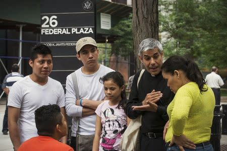 File photo of Father Arias, an advocate with New Sanctuary Coalition of New York City, speaking with immigrants following their immigration hearings at the U.S. Federal Building in New York