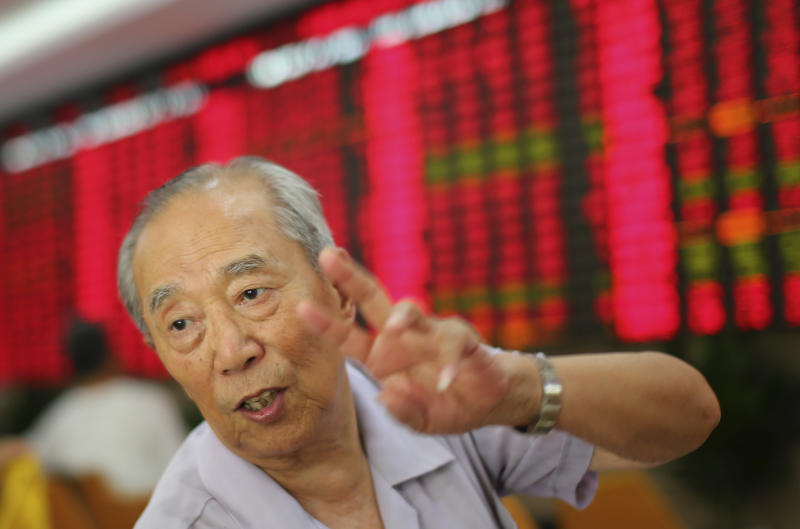 An investor gestures at a private securities company on Monday July 15, 2013 in Shanghai, China. Asian stock markets posted modest gains Monday, registering relief that a slowdown in China's economic growth wasn't as sharp as feared. (AP Photo)