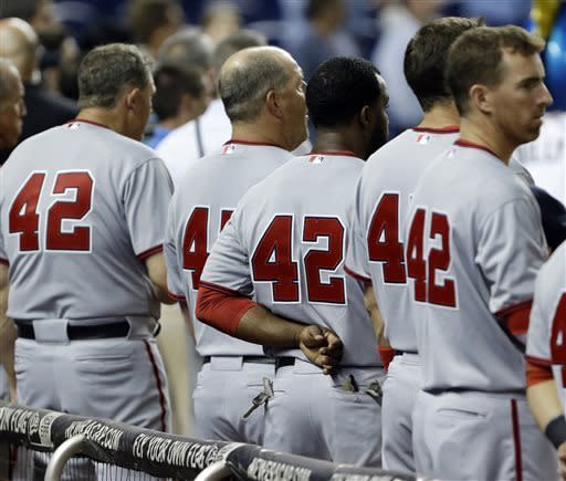 Washington Nationals players wear No. 42 in honor of Jackie Robinson during the singing of the national anthem before the start of a baseball game against the Miami Marlins, Monday, April 15, 2013 in Miami. Baseball is celebrating its fifth Jackie Robinson Day the 66th anniversary of his breaking baseball's racial barrier with the Brooklyn Dodgers. (AP Photo/Wilfredo Lee)