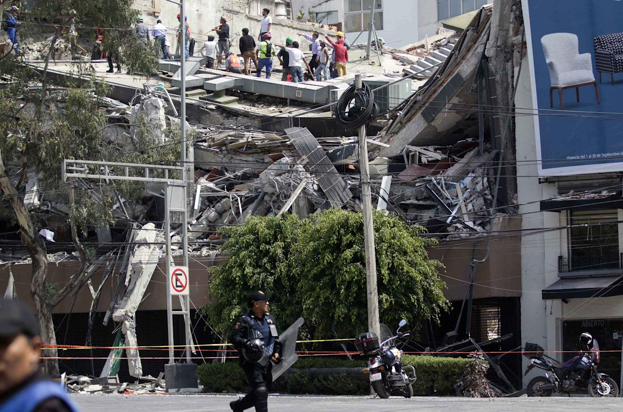 <p>Volunteers and rescuers work on the roof of a building after the deadly earthquake in Mexico City (Rex features) </p>