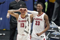 Alabama's Jahvon Quinerly (13) and John Petty Jr. (23) celebrate in the final moments of Alabama's win over Mississippi State in an NCAA college basketball game in the Southeastern Conference Tournament Friday, March 12, 2021, in Nashville, Tenn. (AP Photo/Mark Humphrey)