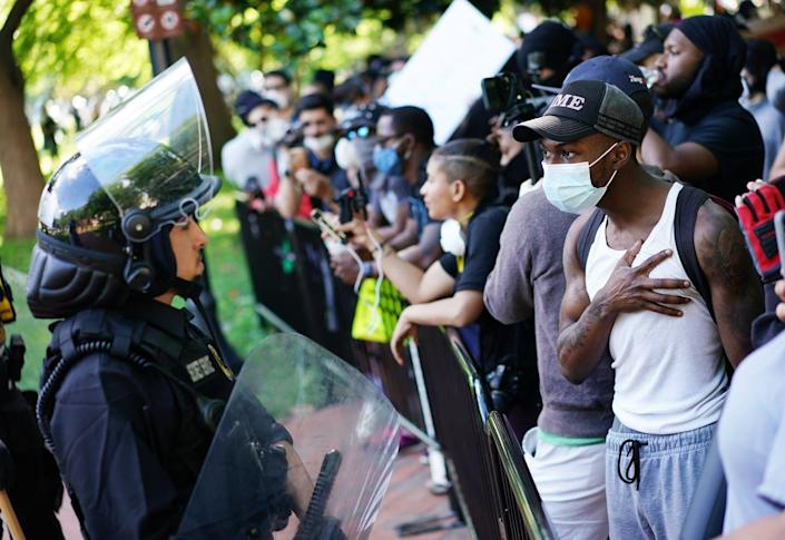 "<span class=""caption"">Protesters against racist police violence encounter police in Washington, D.C., on May 31.</span> <span class=""attribution""><a class=""link rapid-noclick-resp"" href=""https://www.gettyimages.com/detail/news-photo/demonstrators-protesting-the-death-of-george-floyd-talk-to-news-photo/1216617277"" rel=""nofollow noopener"" target=""_blank"" data-ylk=""slk:Mandel Ngan/AFP via Getty Images"">Mandel Ngan/AFP via Getty Images</a></span>"