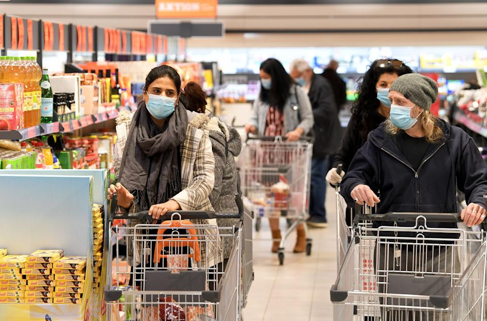 Customers wear face protection in a supermarket in Vienna on April 6, 2020. - As of today, April 6, 2020, it is mandatory in Austria to wear such protection in supermarkets with a sales area of 400 m2 or more. (Photo by ROLAND SCHLAGER / APA / AFP) / Austria OUT (Photo by ROLAND SCHLAGER/APA/AFP via Getty Images)