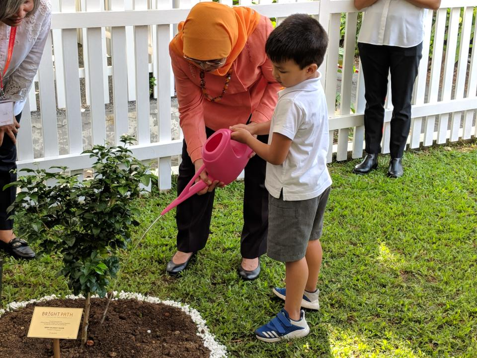 (Guest-of-Honour and President Halimah Yacob, along with Russell, watering a planted sapling on 27 July, 2018, to commemorate the school's official opening. PHOTO: Wong Casandra/Yahoo News Singapore)