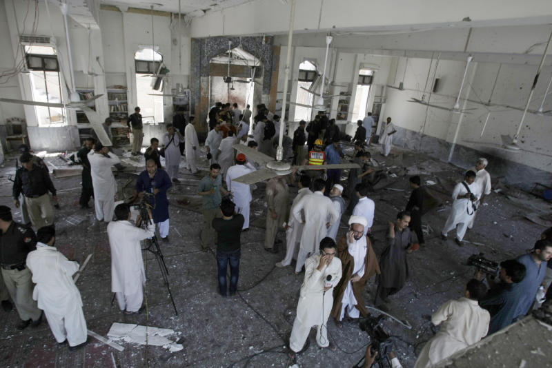 People gather at a Shiite mosque targeted by a suicide bomber in Peshawar, Pakistan on Friday, June 21, 2013. Militants opened fire on a Shiite Muslim mosque where worshippers were gathering for Friday prayers, and then a suicide bomber detonated his explosives inside, killing more than a dozen people in the latest attack aimed at the minority sect, police said. (AP Photo/Mohammad Sajjad)