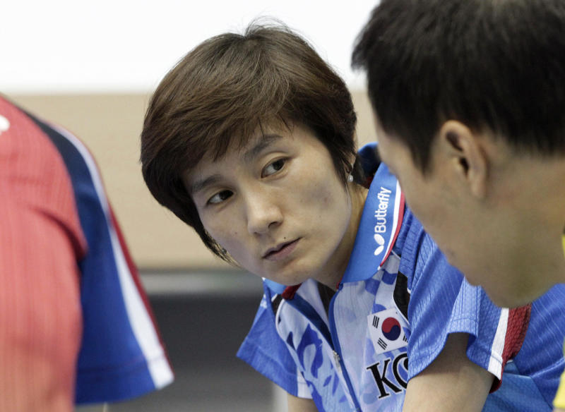 """In this Wednesday, June 27, 2012 photo, Hyun Jung-hwa, the head coach of South Korea's Olympic women table tennis team, left, talks with Yoo Nam-kyu, Olympic men's table tennis team player, at the National Training Center in Seoul, South Korea. South Korean table tennis star Hyun teamed up with North Korean Li Pun Hui in 1991 as part of the first """"unified Korea"""" team to march into international competition wearing the flag of the Korean Peninsula. (AP Photo/Ahn Young-joon)"""