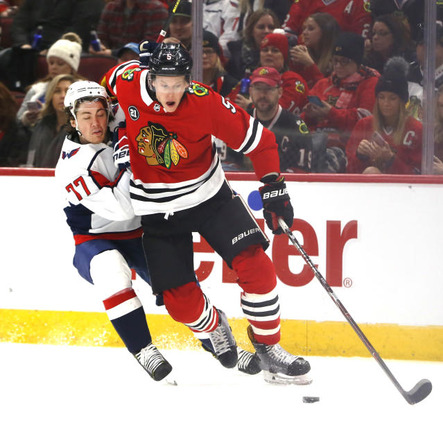 Washington Capitals right wing T.J. Oshie (77) and Chicago Blackhawks defenseman Connor Murphy (5) battle for the puck during the first period of an NHL hockey game Sunday, Jan. 20, 2019, in Chicago. (AP Photo Nuccio DiNuzzo)