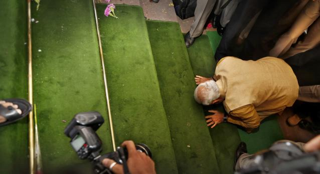 FILE - In this May 20, 2014 file photo, India's next prime minister and Hindu nationalist Bharatiya Janata Party (BJP) leader Narendra Modi, bends down on his knees on the steps of the Indian parliament building as a sign of respect as he arrives for the BJP parliamentary party meeting in New Delhi, India. Indian Prime Minister Narendra Modi's party claimed it had won re-election with a commanding lead in vote count Thursday, May 23, 2019. Modi, 68, the leader of the Hindu nationalist Bharatiya Janata Party, has carefully constructed an image of himself as a pious man of the people, a would-be monk called to politics who has elevated India's status globally and transformed its parliamentary elections from a contest of political parties on social and economic issues into a cult of personality. (AP Photo/Manish Swarup, File)