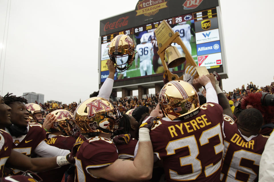 FILE - In this Nov. 9, 2019, file photo, Minnesota football players hold up the Governor's Victory Bell after winning 31-26 against Penn State during an NCAA college football game in Minneapolis. Big Ten is going to give fall football a shot after all. Less than five weeks after pushing football and other fall sports to spring in the name of player safety during the pandemic, the conference changed course Wednesday, Sept. 16, 2020, and said it plans to begin its season the weekend of Oct. 23-24. (AP Photo/Stacy Bengs, File)