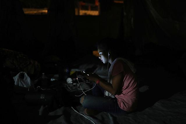 <p>A Central American migrant from El Salvador participating in the Migrant Stations of the Cross caravan is lit up by her cell phone during the caravan's few-day's stop at a sports center in Matias Romero, Oaxaca state, Mexico, late Monday, April 2, 2018. (Photo: Felix Marquez/AP) </p>