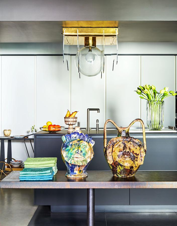 "<div class=""caption""> A 1970s light fixture hangs in the kitchen. Sicilian ceramic vases. </div> <cite class=""credit"">Oberto Gili</cite>"