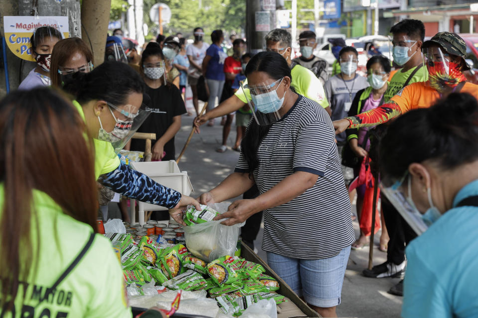 "A woman receives free food at a makeshift stall called ""Community Pantry"" beside a road in Quezon city, Philippines on Monday, April 19, 2021. Donated food and other essential items from residents or volunteers are placed on makeshift stalls for people who need it as many have lost jobs due to quarantine measures set by the government to curb the surge in COVID-19 cases in the country. The ""Community Pantry"" which started in Maginhawa street has spread to several areas around the metropolitan to support people struggling to make ends meet. (AP Photo/Aaron Favila)"