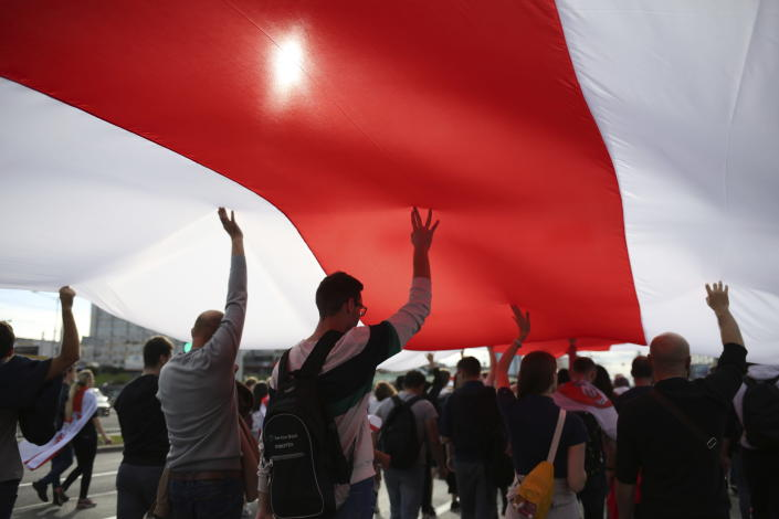 Protesters carry a giant old Belarusian national flag during a Belarusian opposition supporters' rally protesting the official presidential election results in Minsk, Belarus, Sunday, Sept. 13, 2020. Protests calling for the Belarusian president's resignation have broken out daily since the Aug. 9 presidential election that officials say handed him a sixth term in office. (TUT.by via AP)