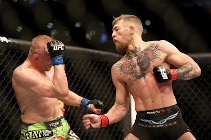 Conor McGregor delivers a punch to Dennis Siver during their fight. (AP)