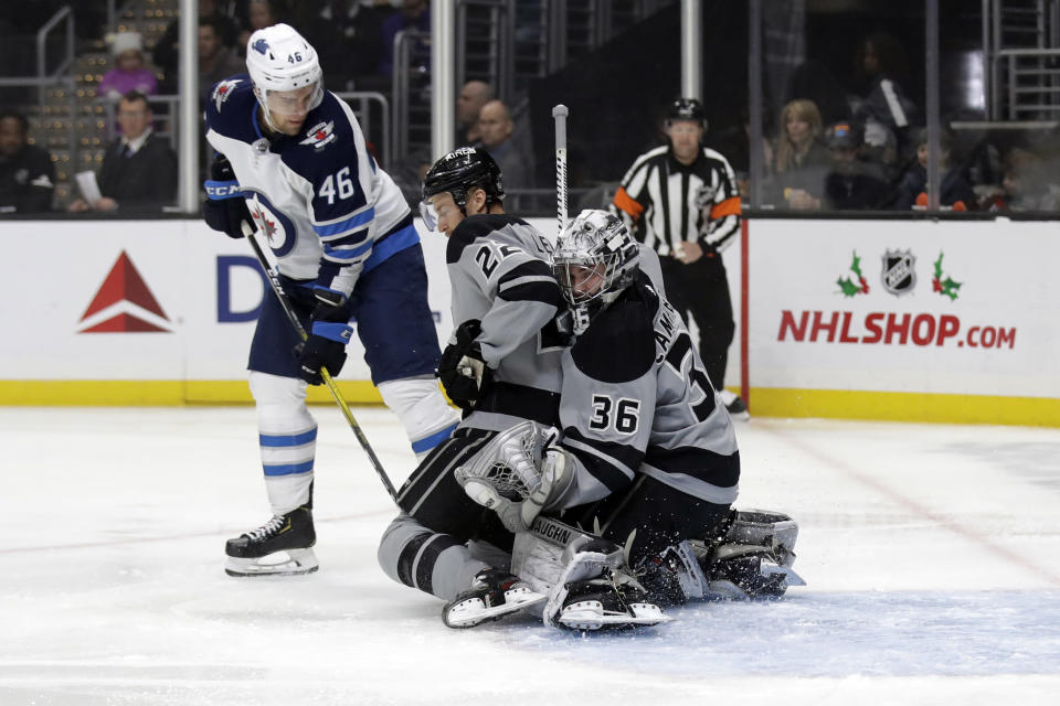 Los Angeles Kings' Trevor Lewis, center, teams up with goaltender Jack Campbell (36) to stop a shot from Winnipeg Jets' Joona Luoto (46) during the first period of an NHL hockey game Saturday, Nov. 30, 2019, in Los Angeles. (AP Photo/Marcio Jose Sanchez)