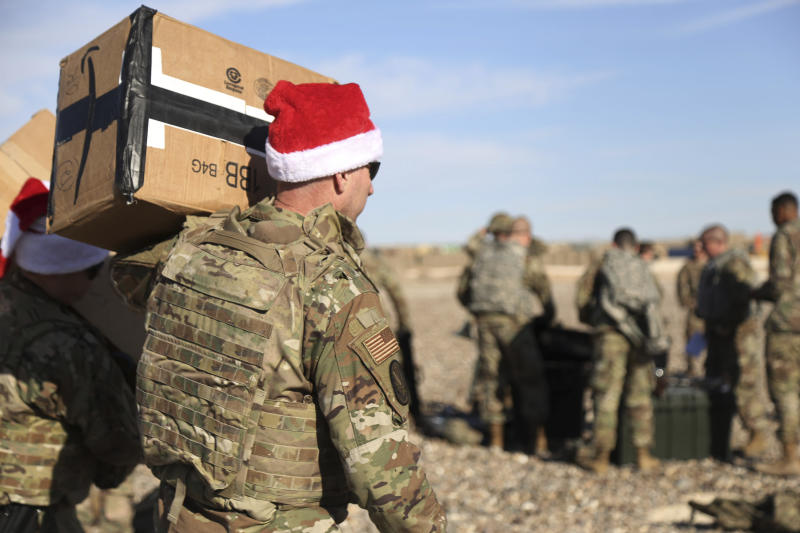In this Monday, Dec. 23, 2019, photo, a U.S. soldier carries Christmas gifts from a helicopter to deliver to his comrades on a base near the al-Omar oilfield in eastern Syria. It's an operation is called Holiday Express - in addition to delivering presents, the U.S.-led coalition forces brought a U.S. military band to play Christmas carols and music to several bases in eastern Syria. (AP Photo/Farid Abdul-Wahid)