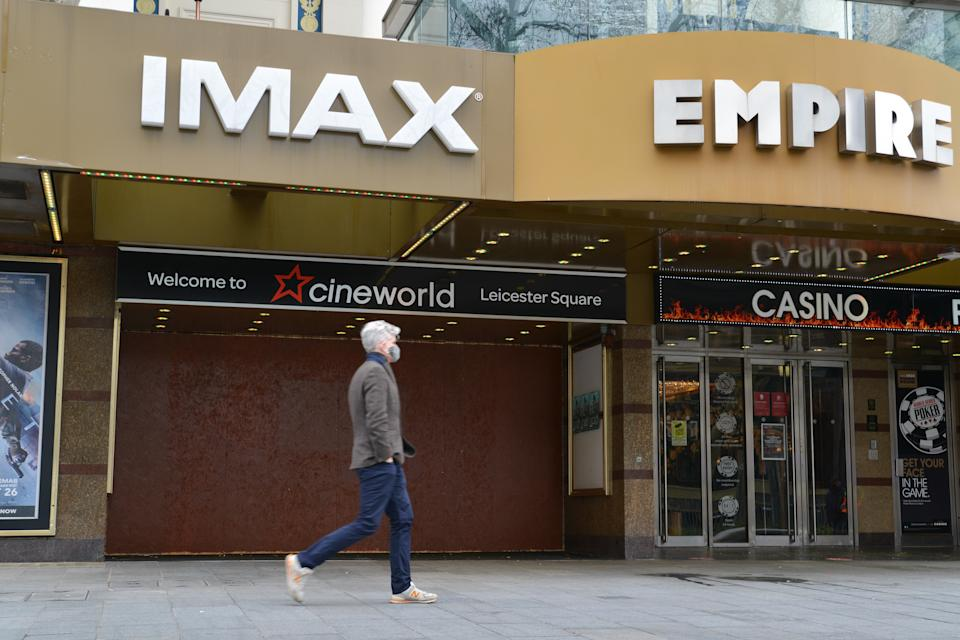 LONDON, UNITED KINGDOM - 2021/01/18: A man wearing a face mask walks past a boarded-up Cineworld, which was closed due to COVID19 pandemic at the Leicester Square in London. Venues and businesses in London are undergoing shutdown during the pandemic restrictions amid the third London lockdown. (Photo by Thomas Krych/SOPA Images/LightRocket via Getty Images)