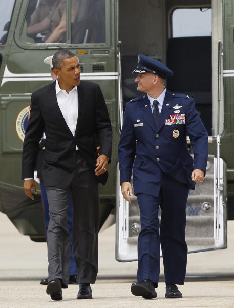 President Barack Obama walks from Marine One with Air Force Col. William Knight to board Air Force One, Saturday, Aug. 11, 2012, in Andrews Air Force Base, Md., en route to Chicago. (AP Photo/Carolyn Kaster)