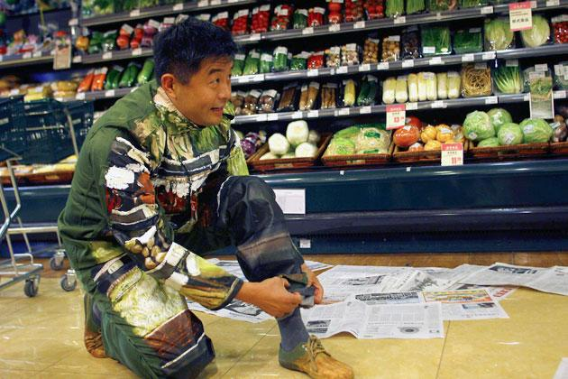Artist Liu Bolin folds his trousers as he prepares to demonstrate an art piece by blending in with the vegetables displayed on the shelves at a supermarket in Beijing, November 10, 2011. Liu, also known as the 'Vanishing Artist', started his optical illusion artworks of becoming 'invisible' more than six years ago. Picture taken November 10, 2011. REUTERS/China Daily