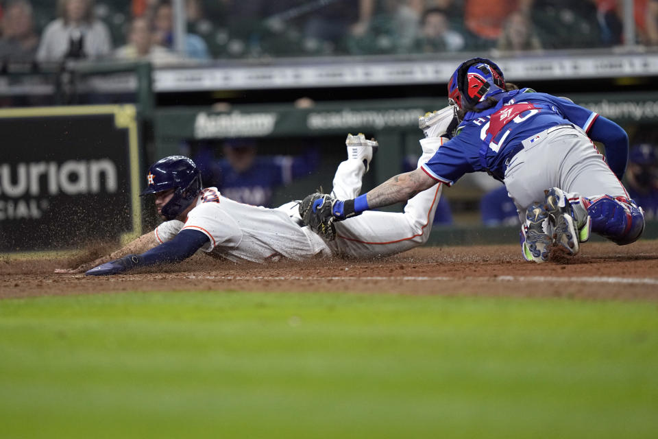 Houston Astros' Chas McCormick, left, is tagged out at home plate by Texas Rangers catcher Jose Trevino (23) during the 10th inning of a baseball game Thursday, May 13, 2021, in Houston. (AP Photo/David J. Phillip)