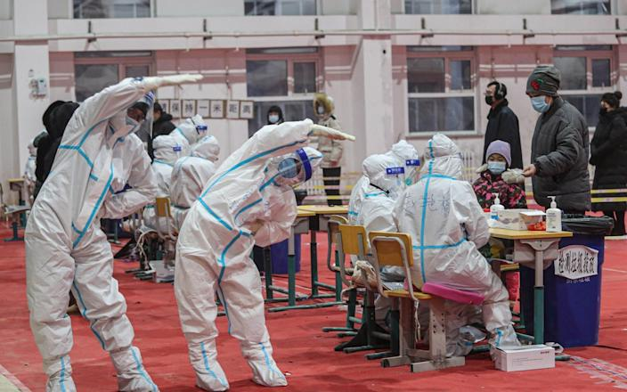 Medical workers wearing protective suits work out at a temporary COVID-19 testing center on January 5, 2021 in Shenyang