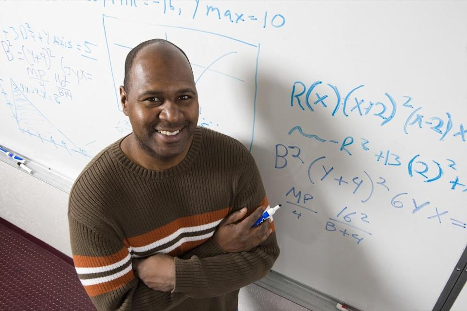 portrait of confident teacher solving math's equations on whiteboard in classroom