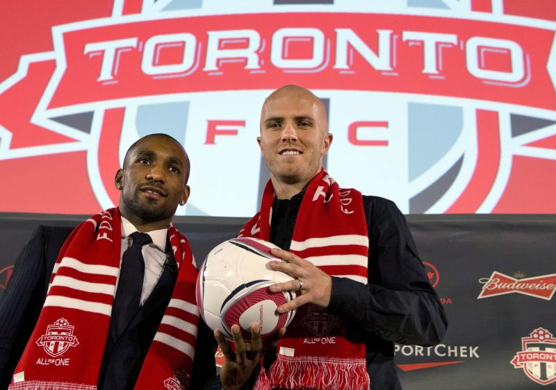 New Toronto FC soccer players Jermain Defoe, left, and Michael Bradley pose during a news conference in Toronto, Monday, Jan. 13, 2014. (AP Photo/The Canadian Press, Frank Gunn)