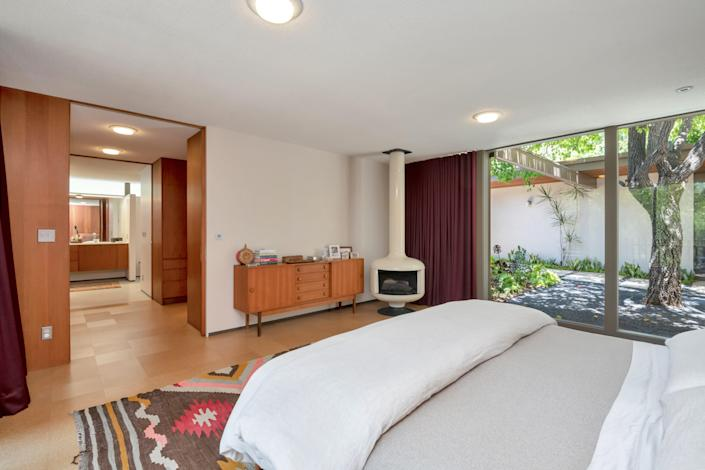 The main bedroom features large windows and a freestanding fireplace.