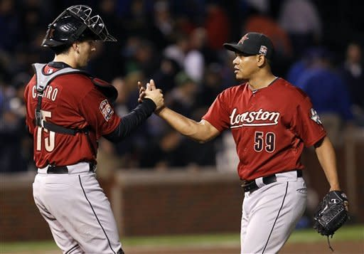 Houston Astros catcher Jason Castro (15) and relief pitcher Wilton Lopez celebrate their 3-0 win over the Chicago Cubs after a baseball game, Tuesday, Oct. 2, 2012, in Chicago. (AP Photo/Charles Rex Arbogast)
