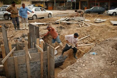 Iraqis workers repair sewage line in eastern Mosul