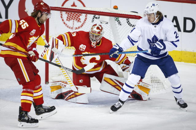 Toronto Maple Leafs' Kasperi Kapanen, right, tries to tip the puck past Calgary Flames goalie David Rittich, center, as Noah Hanifin looks on during the first period of an NHL hockey game, Thursday, Dec. 12, 2019 in Calgary, Alberta. (Jeff McIntosh/The Canadian Press via AP)
