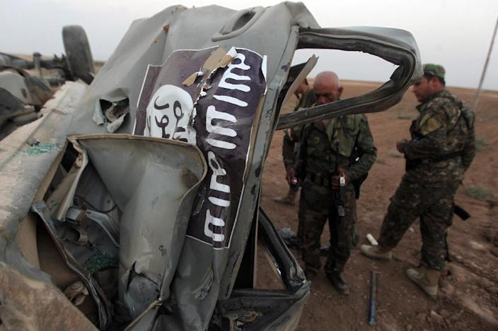 Peshmerga fighters inspect the remains of a car bearing an image of the Islamic State (IS) flag in Mosul, Iraq on August 18,2014 (AFP Photo/Ahmad al-Rubaye)
