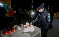 An Estonian police officer wearing a protective face mask cuts a cake at border crossing point in Ikla