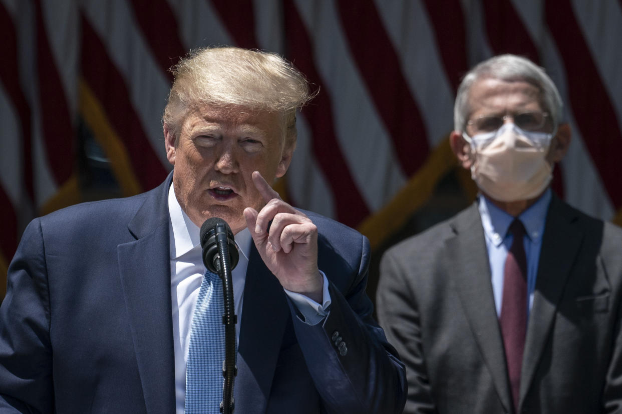 Dr. Anthony Fauci (R), director of the National Institute of Allergy and Infectious Diseases, looks on as U.S. President Donald Trump delivers remarks about coronavirus vaccine development in the Rose Garden of the White House on May 15, 2020 in Washington, DC.(Drew Angerer/Getty Images)