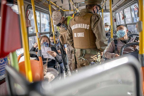 PHOTO: Authorities verify the health permits of the passengers on a public transport bus in Santiago, Chile. Sanitary checks and police controls were implemented during the first day of total lockdown in the central area of the country.   (SOPA Images/LightRocket via Getty Images, FILE)
