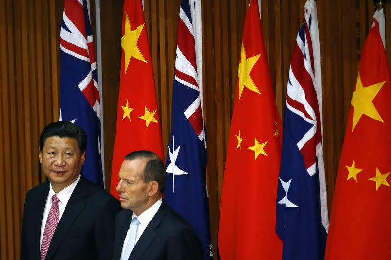 China's President Xi Jinping and Australia's Prime Minister Tony Abbott watch as free trade deals are signed during a signing ceremony in Canberra