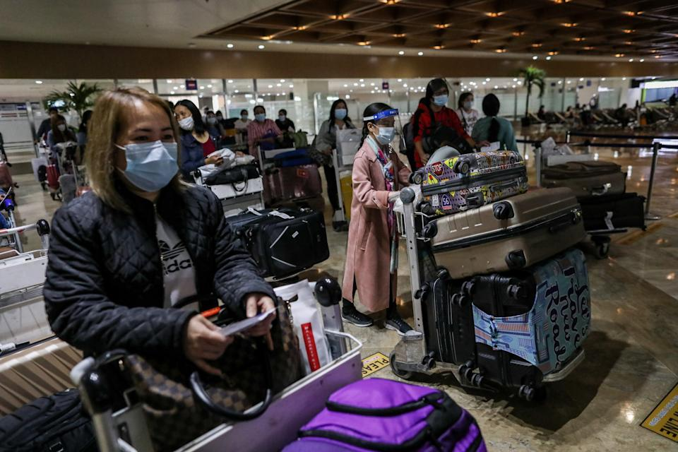 Passengers wearing protective masks to prevent the spread of COVID-19 push their carts as they arrive at Manila's International Airport. Manila, Philippines. (Photo by: Basilio H. Sepe/ Majority World/Universal Images Group via Getty Images)