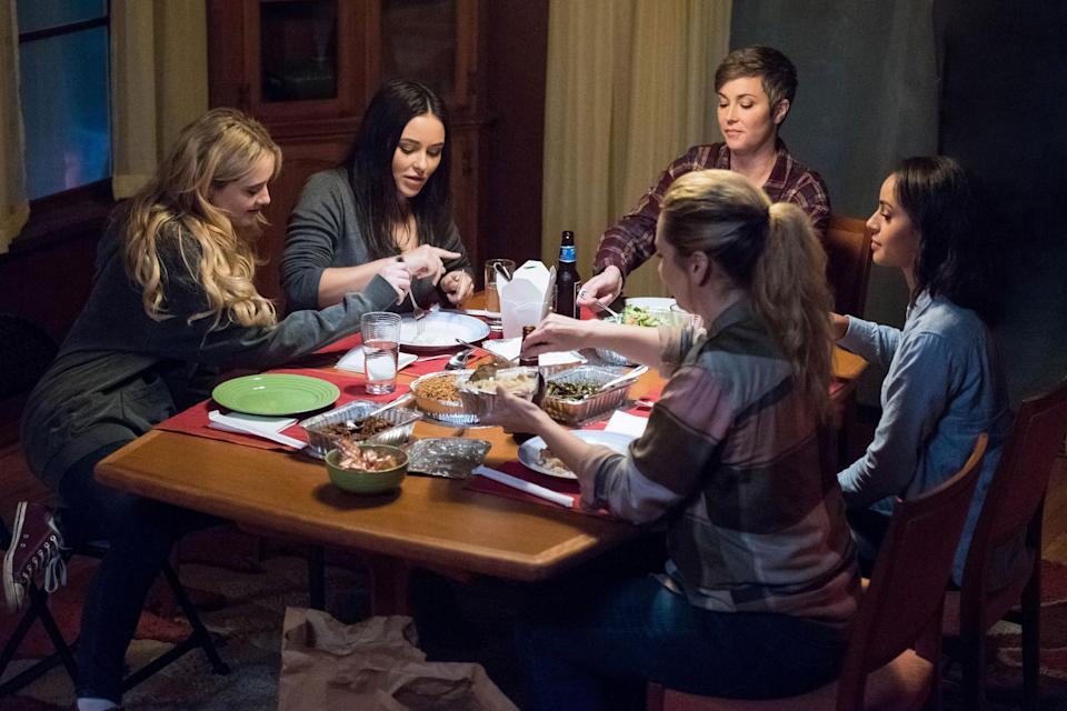 The characters sitting around a table eating