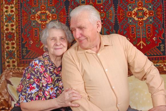 Older couple seated on a couch.