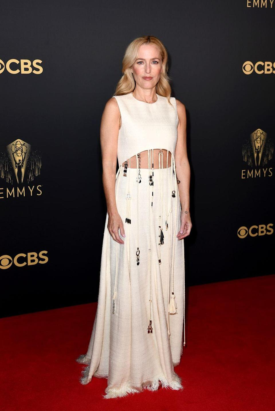 <p>Gillian Anderson had some fun with her 2021 Emmy look, wearing a white gown by Chloé with a cut-out detail and plenty of fringing.</p>