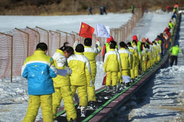 A Chinese student carries the national flag and a 2022 Oympic bid flag on January 16, 2015 at the Shijinglong ski resort in Yanqing, in the suburbs of Beijing (AFP Photo/Wang Zhao)