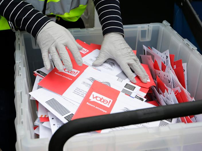 FILE - In this March 10, 2020, file photo wearing gloves, a King County Election worker collect ballots from a drop box in the Washington State primary in Seattle. Washington is a vote by mail state. A new poll from The Associated Press-NORC Center for Public Affairs Research finds Democrats are now much more likely than Republicans to support their state conducting elections exclusively by mail, 47% to 29%. (AP Photo/John Froschauer, File)