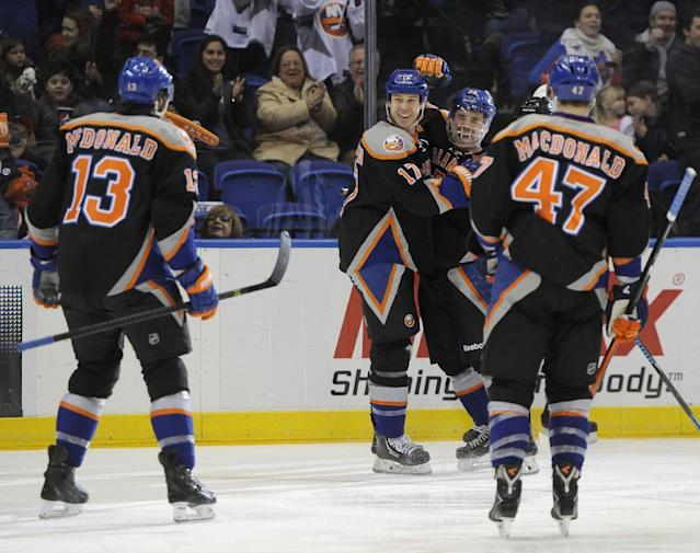 New York Islanders' Colin McDonald (13) and Andrew MacDonald (47) skate in to join Matt Martin (17) and Casey Cizikas (53) to celebrate Martin's goal against the St. Louis Blues in the second period of an NHL hockey game on Saturday, Jan. 25, 2014, in Uniondale, N.Y. (AP Photo/Kathy Kmonicek)