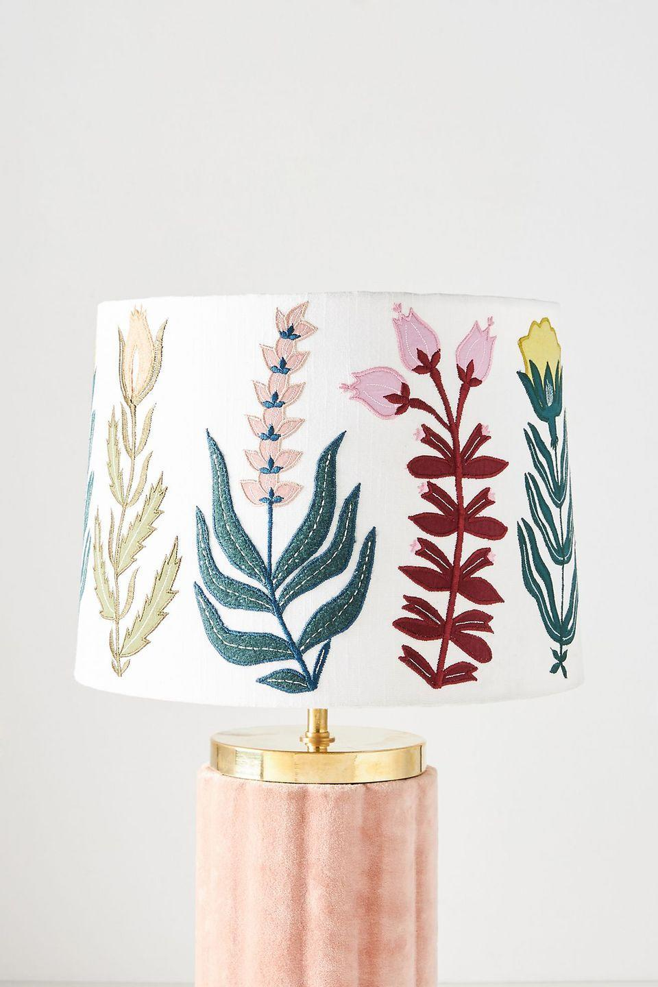 """<p>Adorned with embroidered floral motifs that play over the pure cotton shade, this Anthropologie design will transform any lamp base into a feature piece. We think it's perfect on a plain pink or white base to let the colourful pattern shine. </p><p><strong>Shop now: <a href=""""https://www.anthropologie.com/en-gb/shop/embroidered-celise-lamp-shade?category=home-lighting&color=000&type=REGULAR&quantity=1"""" rel=""""nofollow noopener"""" target=""""_blank"""" data-ylk=""""slk:Embroidered Celise Lampshade at Anthropologie"""" class=""""link rapid-noclick-resp"""">Embroidered Celise Lampshade at Anthropologie</a></strong></p>"""